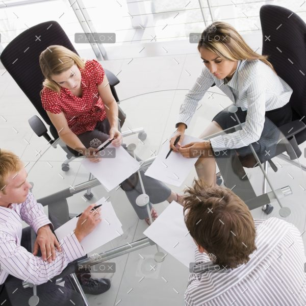 four-businesspeople-in-a-boardroom-with-paperwork-PC4V8H4